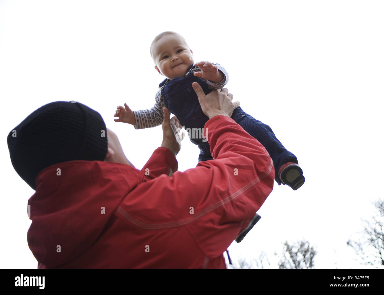 Father baby people throws up man parent paternity jacket red cap headgear love luck feelings emotion fun plays happiness - Stock Image