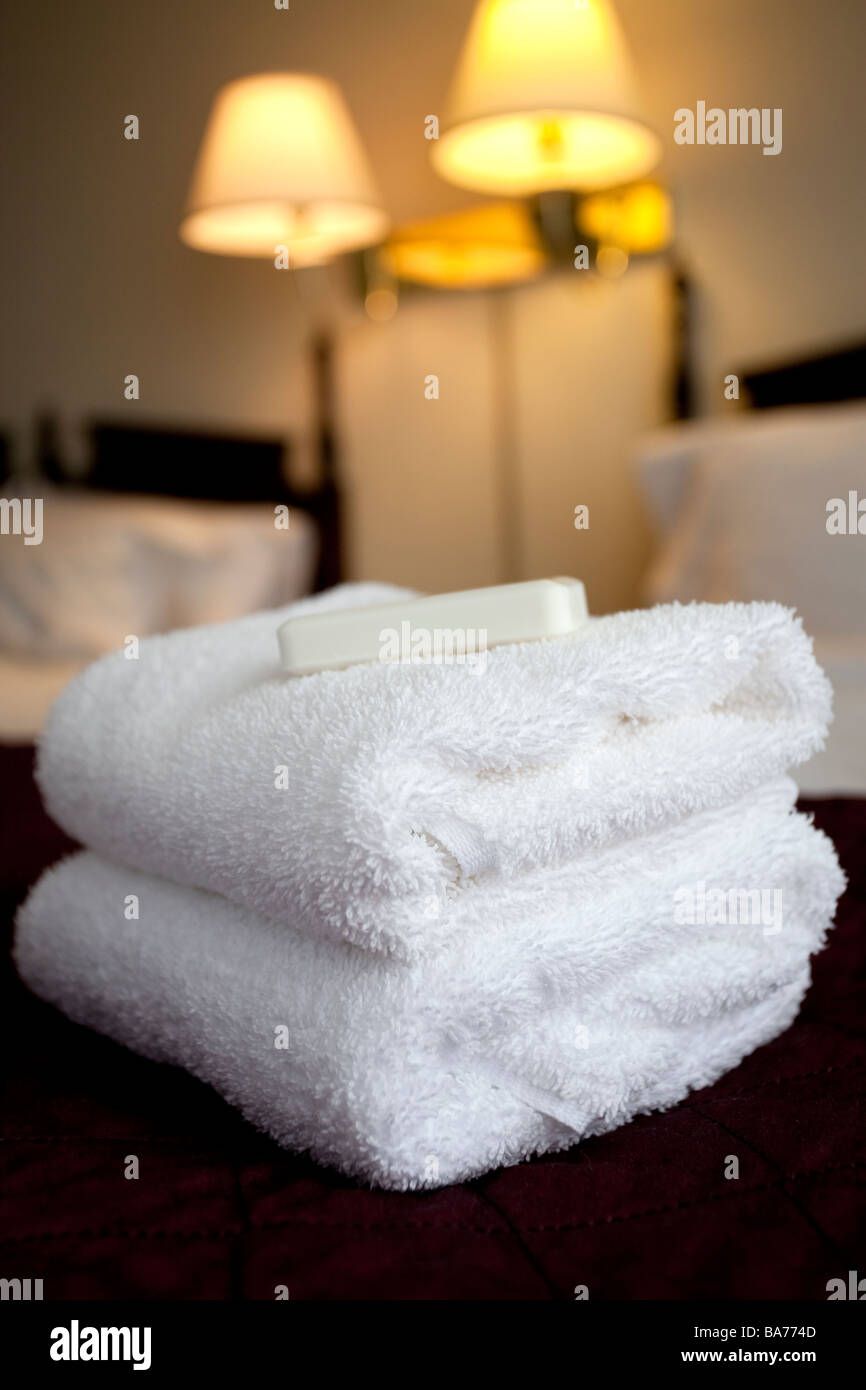 stack of towels and soap on a hotel bed - Stock Image