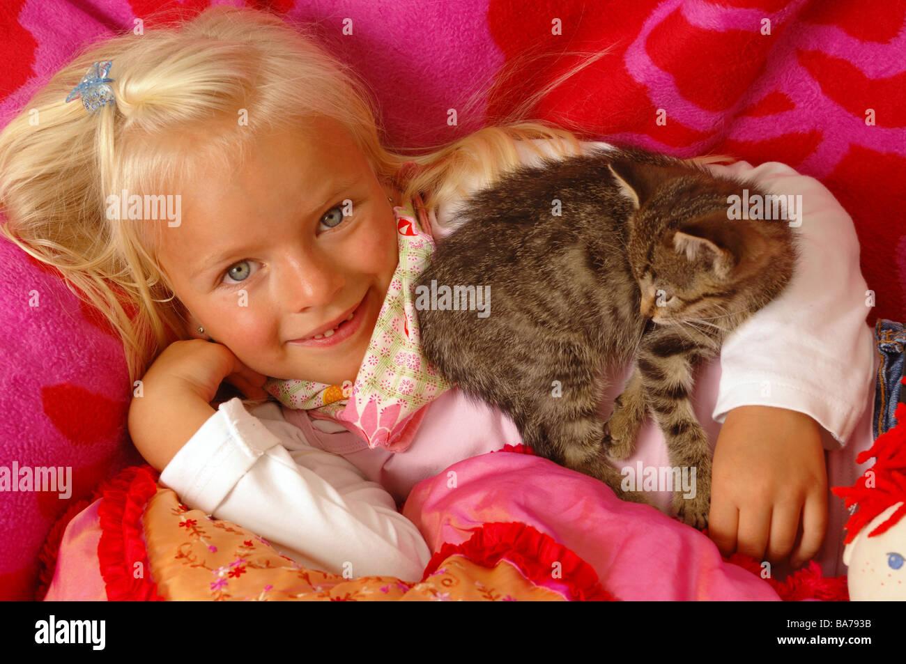 Girls smiles kittens cuddles lies portrait series people 5 years child-portrait child toddler blond gaze camera childhood Stock Photo