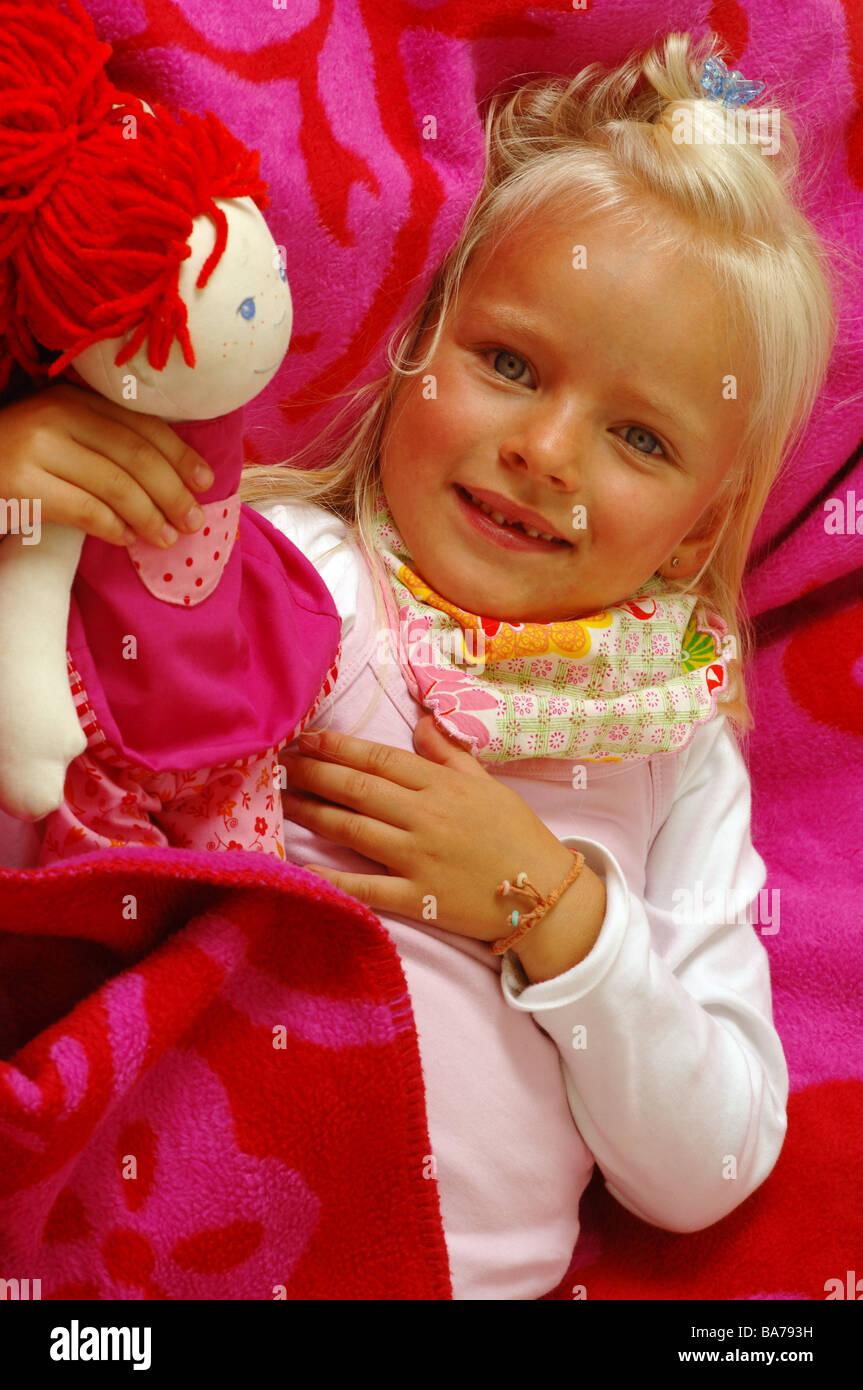Girls smiles doll cuddles lies portrait series people 5 years child-portrait child toddler blond gaze camera scarf childhood Stock Photo