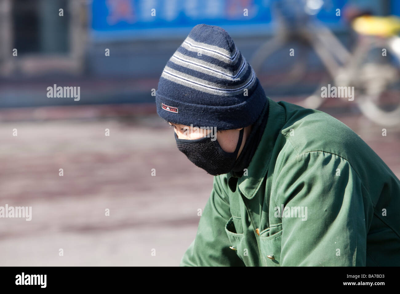 A man wearing a face mask to combat the awful air pollution in Suihua city in Northern China - Stock Image