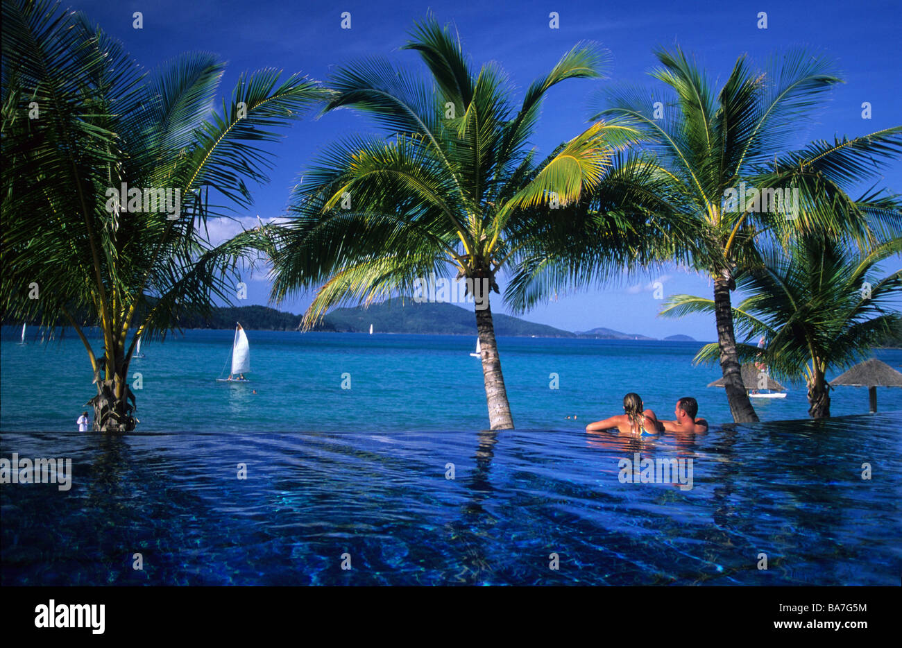 Couple In The Pool Of The Luxury Beach Club Resort On