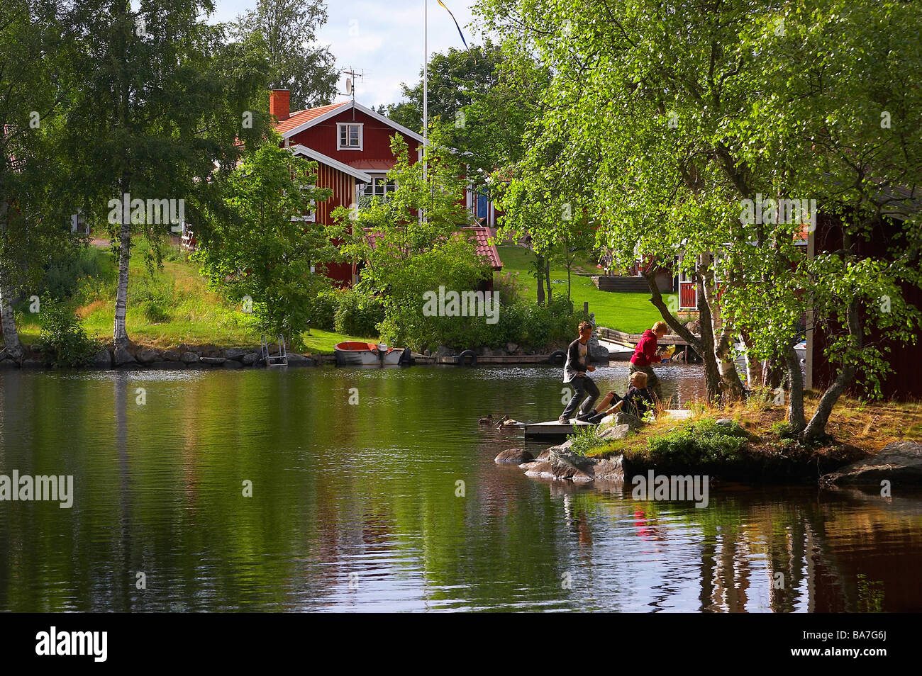 House and children, playing at the bank in Sundborn, Dalarna, middle Sweden - Stock Image