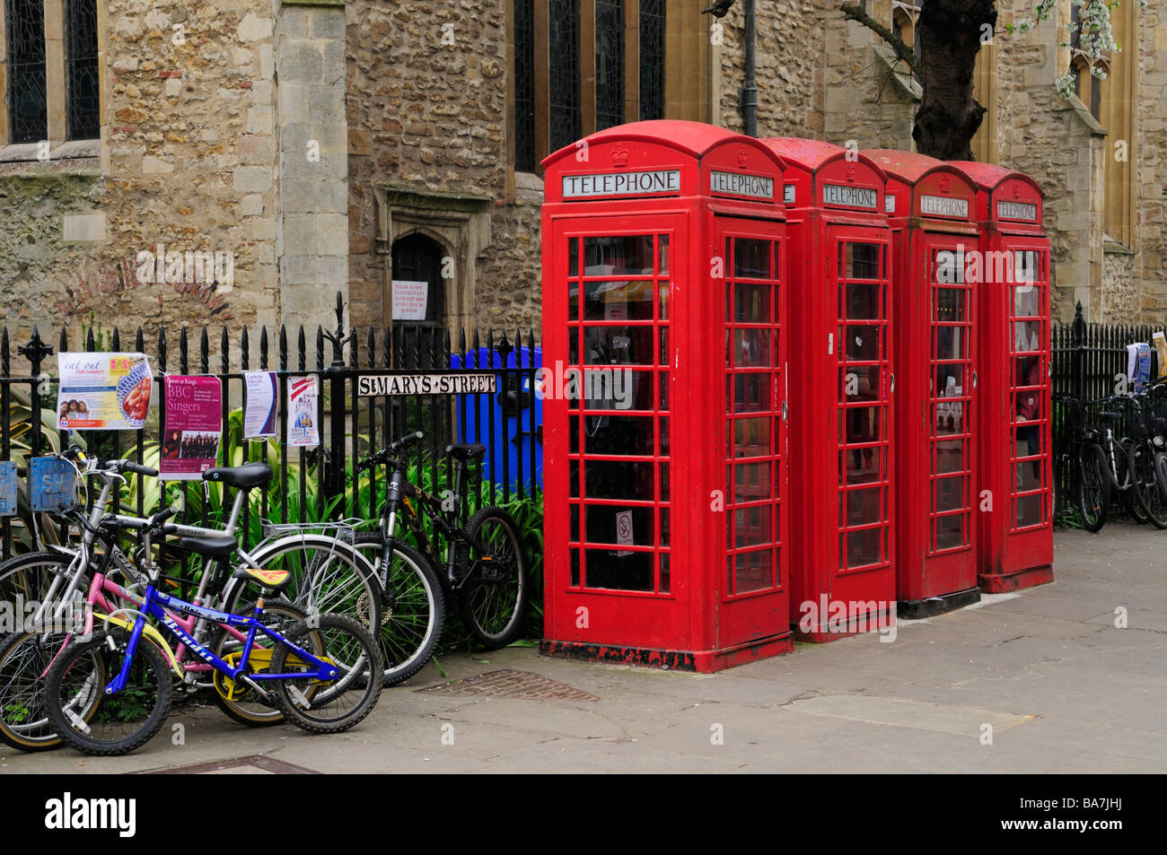 Group of four telephone boxes and bicycles outside Great St Marys Church, Cambridge England Uk - Stock Image