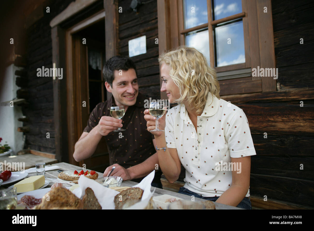 Young couple drinking white wine, Heiligenblut, Hohe Tauern National Park, Carinthia, Austria Stock Photo