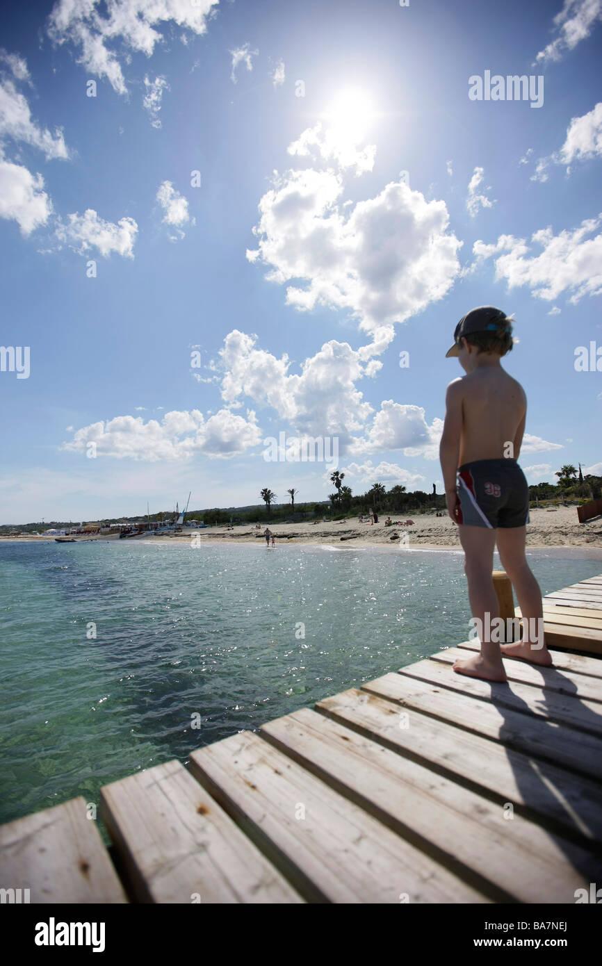 Boy on the jetty at Tahiti beach, St. Tropez, Cote d'Azur, Provence, France - Stock Image