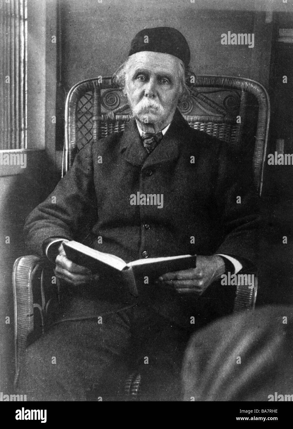 Marshall, Alfred, 26.7.1842 - 12.7.1924, British national economist, half length, sitting in armchair with book, - Stock Image