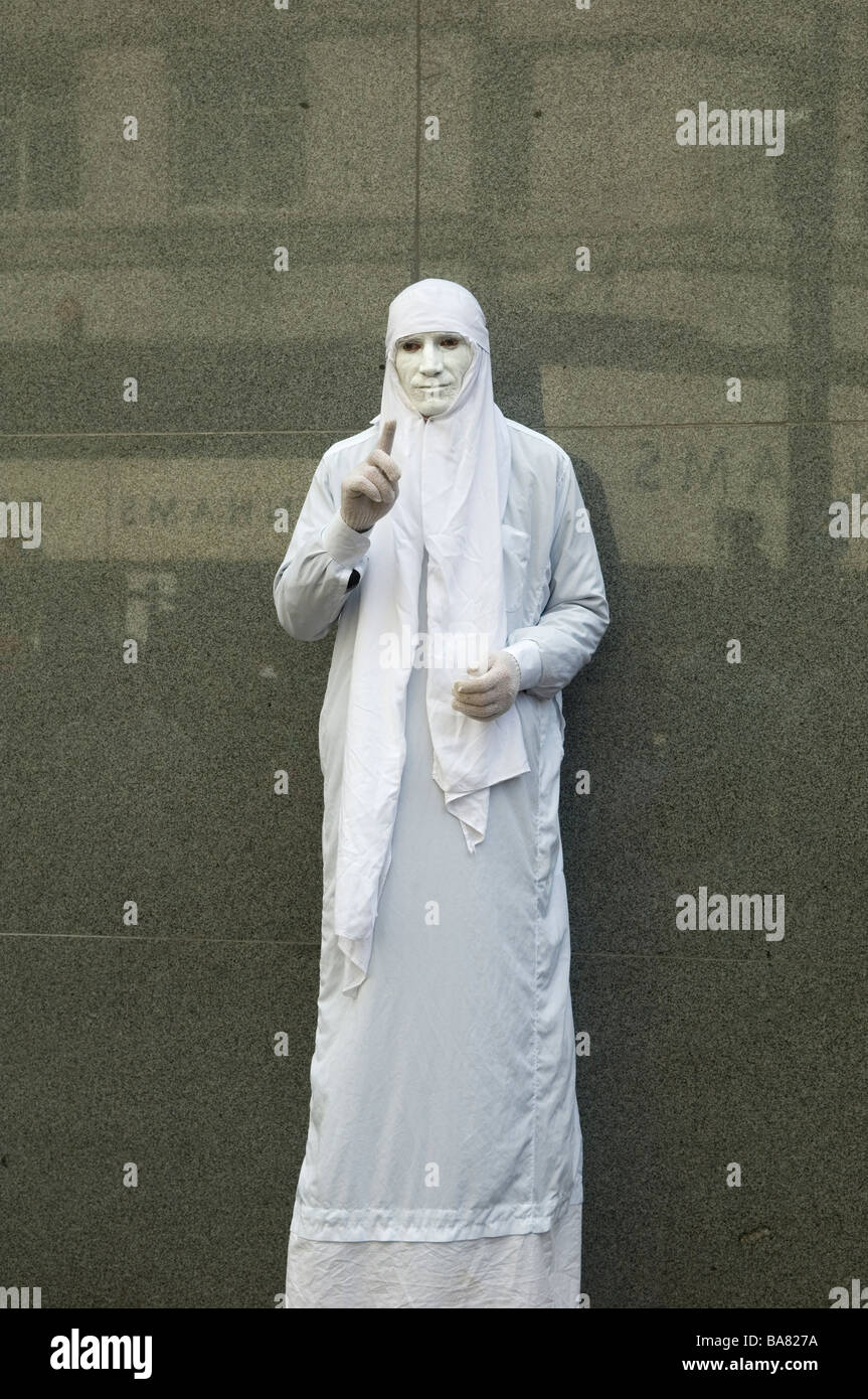 Mime artist with white face paint performing in Manchester city centre UK - Stock Image