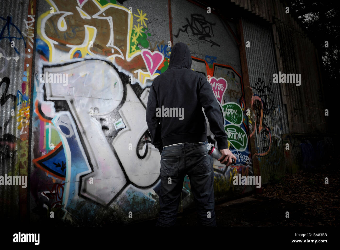 Person in dark clothing standing in front of a graffittied surface - Stock Image