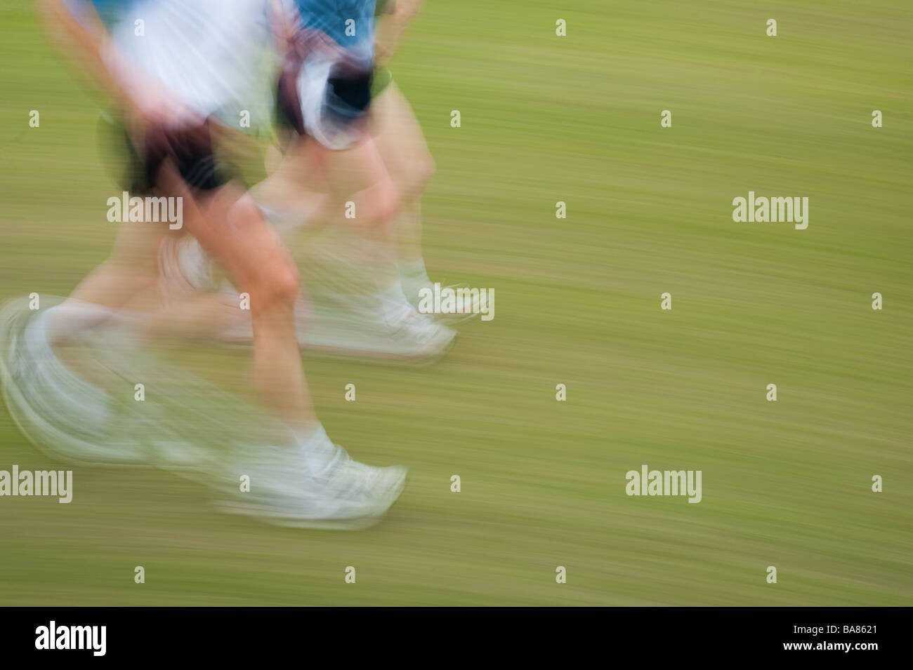 motion blur image of two people running jogging exercising - Stock Image