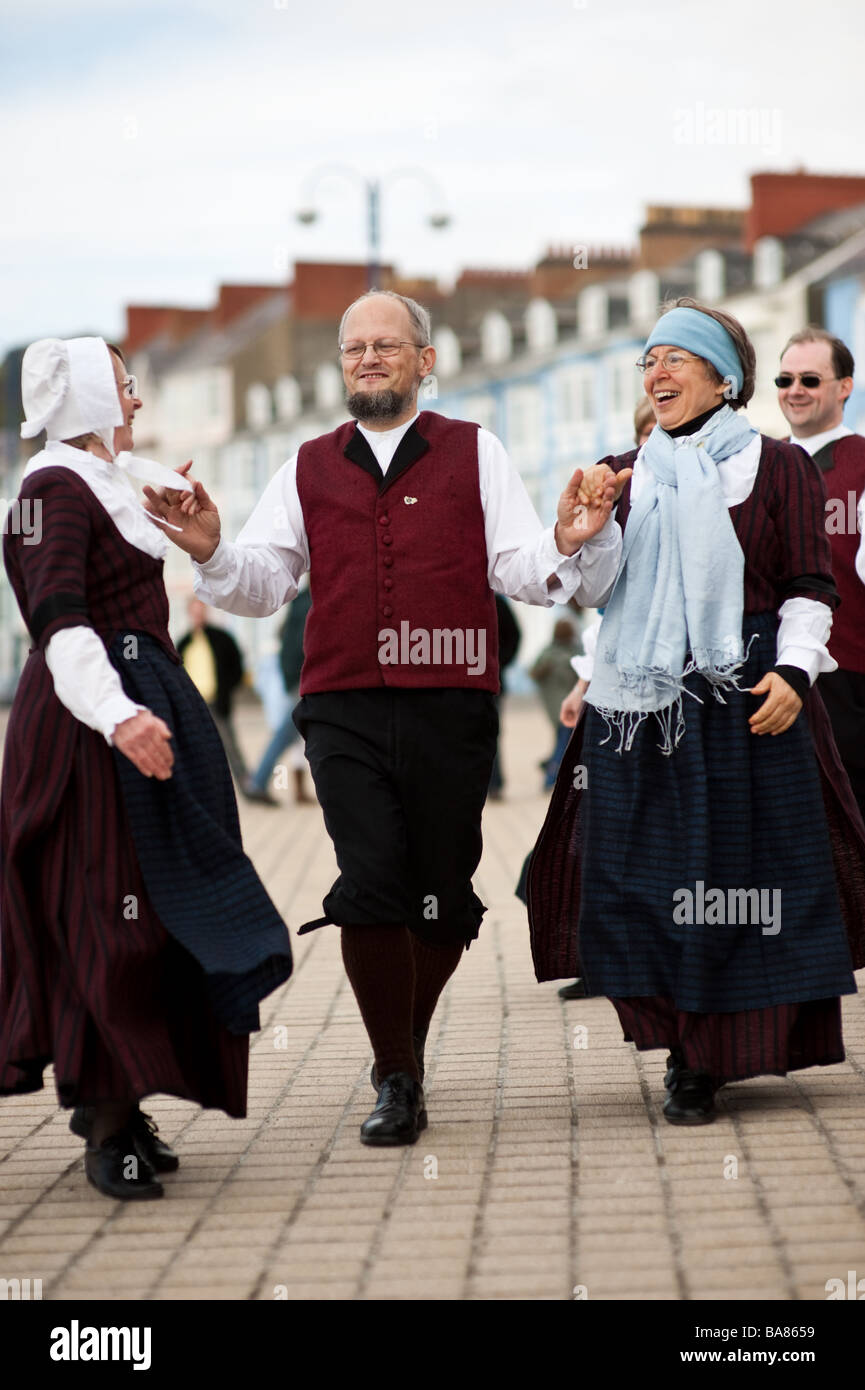 men and women doing traditional welsh folk dancing on the promenade Aberystwyth Ceredigion Wales UK - Stock Image