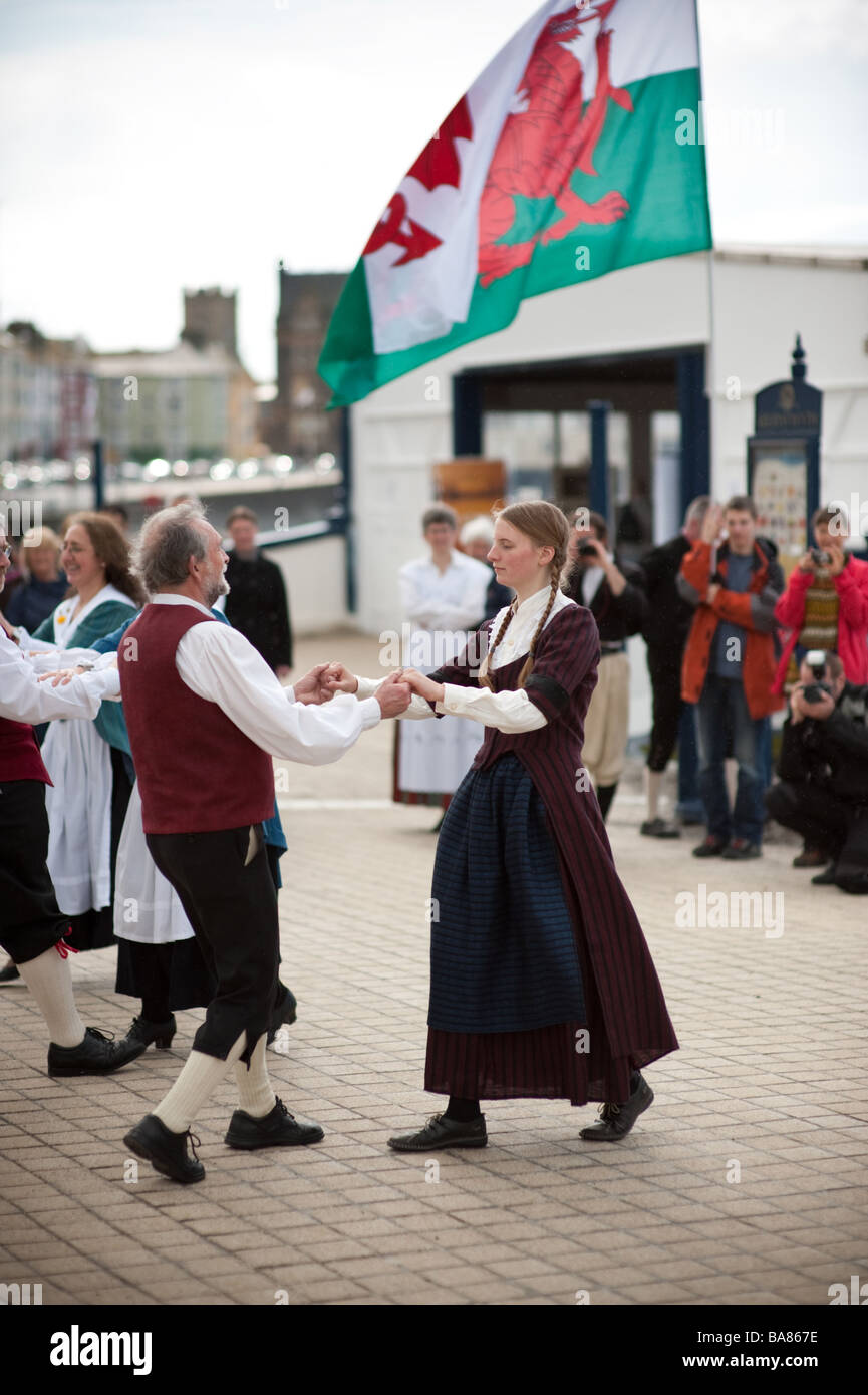 Traditional welsh folk dancing on the promenade Aberystwyth Ceredigion Wales UK with red dragon banner in background - Stock Image