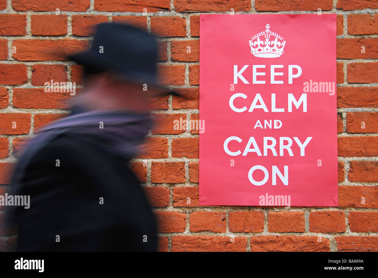 Man walking past a Second World War poster urging people to keep calm and carry on. - Stock Image