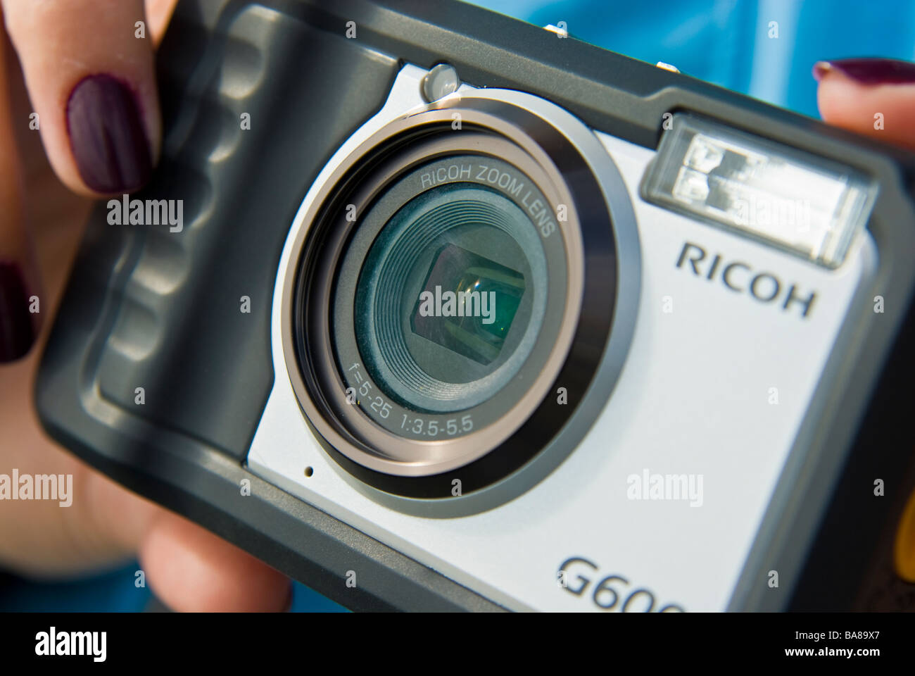Girl with compact digital Camera taking picture | Mädchen fotografiert mit digitaler Kompaktkamera - Stock Image