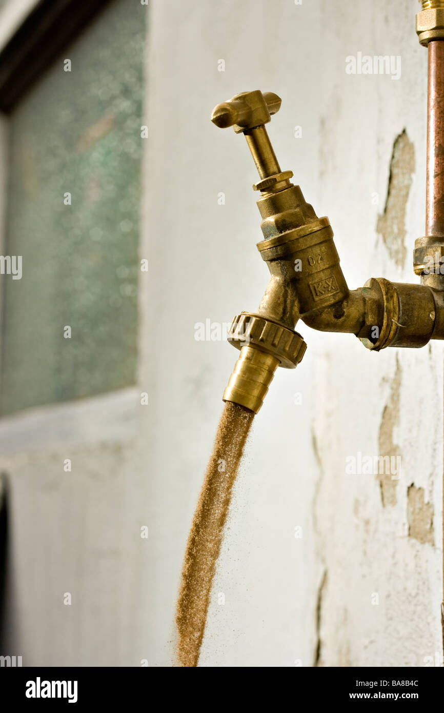 A tap with dust flowing out instead of water with cracked paintwork in the background - Stock Image