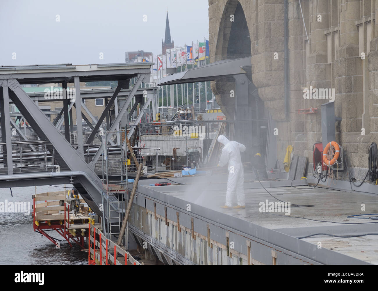 Workman cleaning a quai in the harbour of Hamburg, Germany. - Stock Image