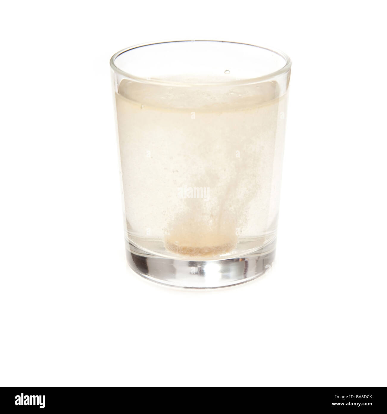Effervescent vitamin C tablet dissolving in a glass of water. Isolated on a white studio background. - Stock Image