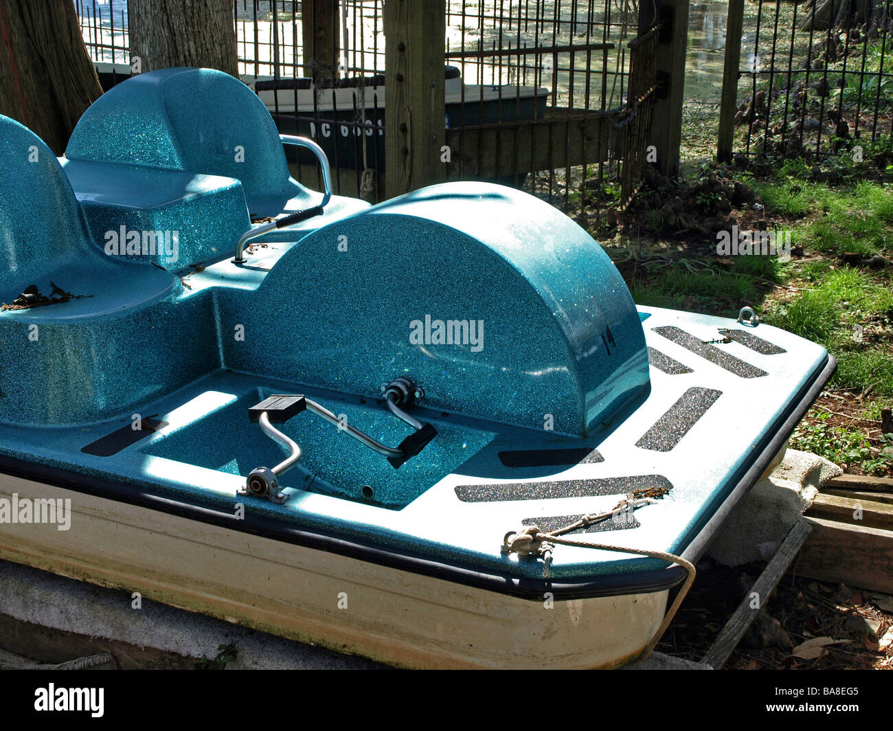 peddle wheel boat peddleboat on shore in deep tourquoise with pedals seats deck and grips - Stock Image