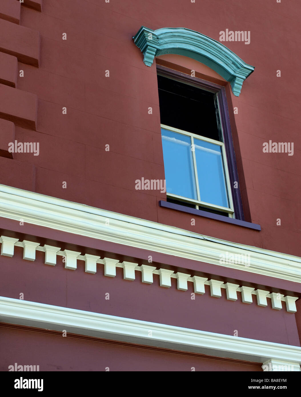 architectural detail orange wall with open window and tourquoise lentel and cream side molding on building, upward - Stock Image