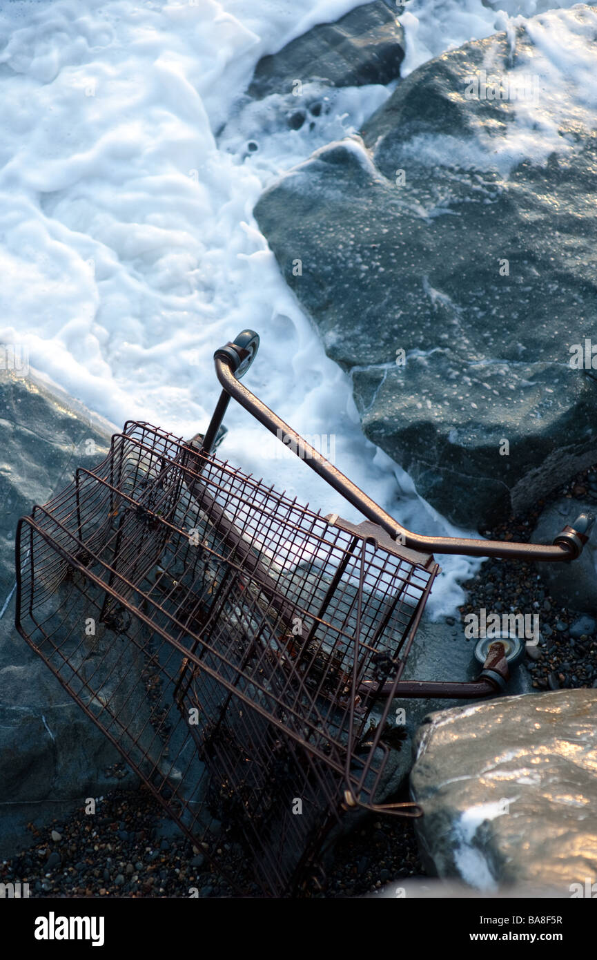 An abandoned rusting shopping trolley on the rocks on the beach washed by the waves - Stock Image