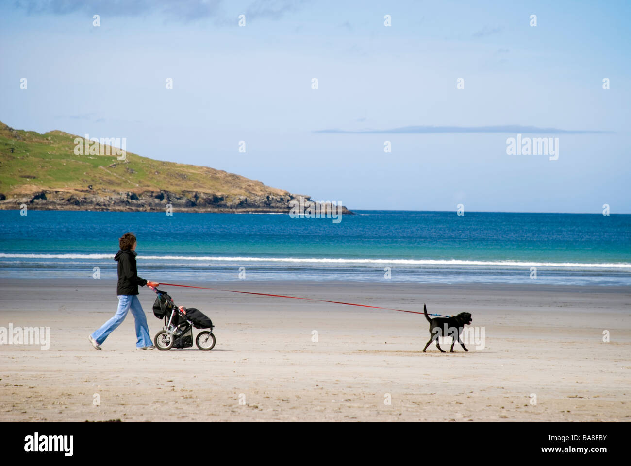 Woman walks a dog and pushes a pushchair by the Atlantic Ocean Stock Photo