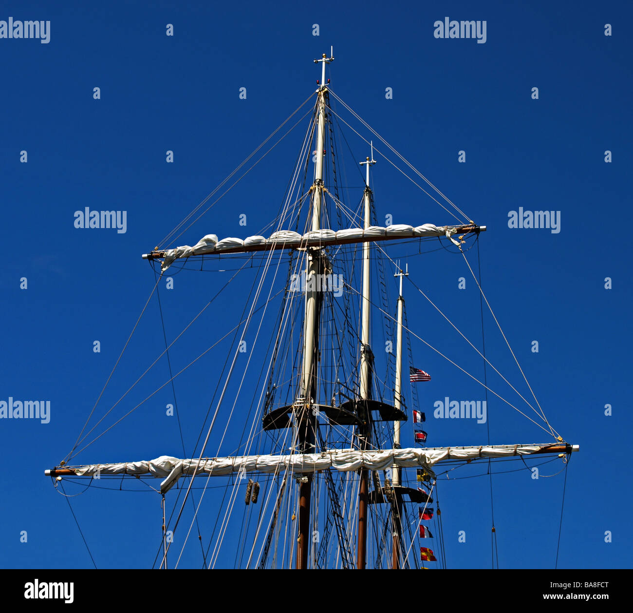 tall-ship tall-ships three masts with furled sails against blue sky with wires and pendants upper part of ship - Stock Image