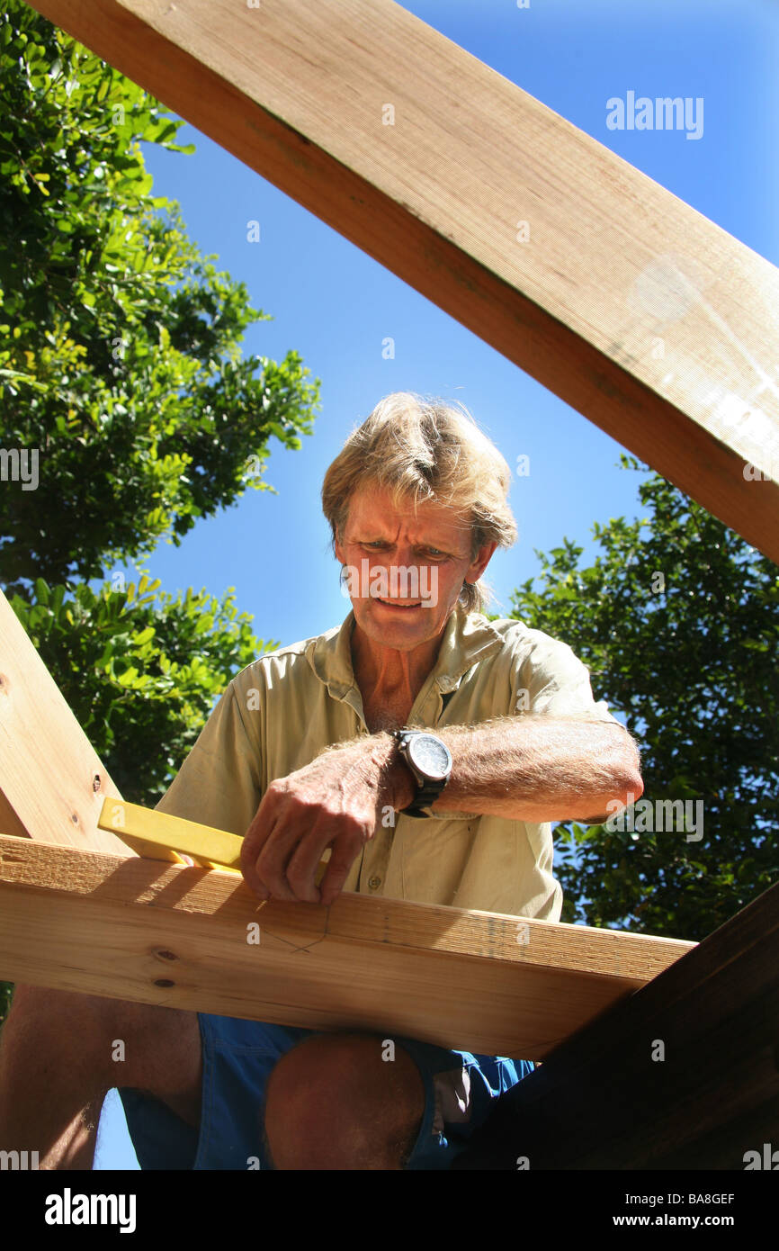 A builder uses geometry to work out angles on a pitch roof - Stock Image
