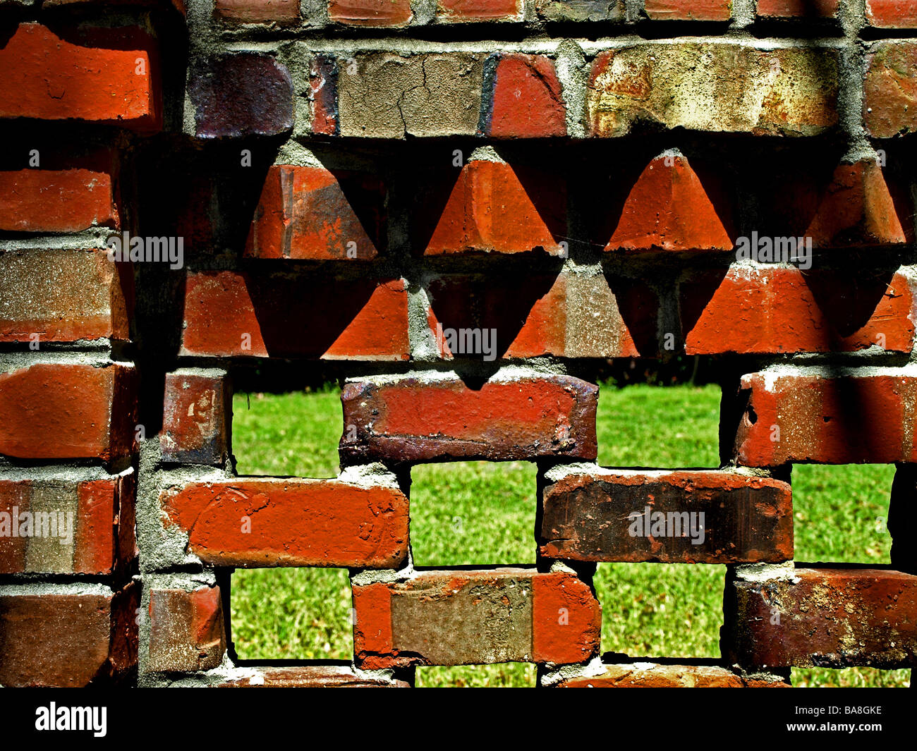brick fence with spaced gaps in wall and bright green grass behind, orange black and shadows with mortor abstract - Stock Image