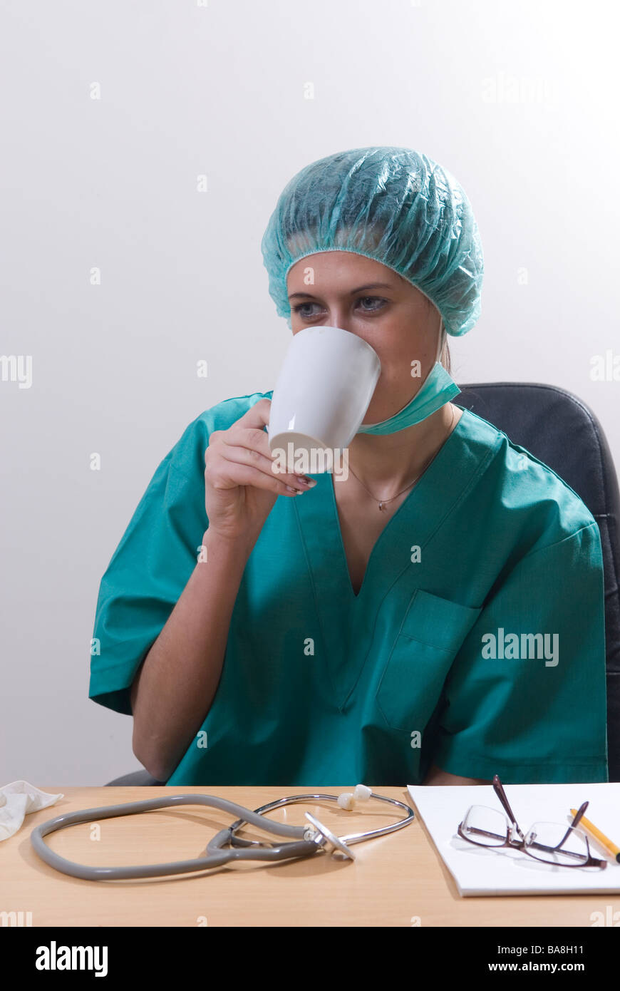 Doctor sat in office drinking coffee Stock Photo