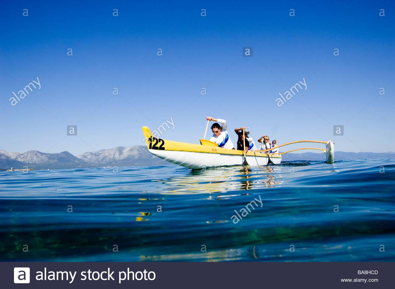 Five Women Paddling a Canoe on Lake Tahoe, California - Stock Image