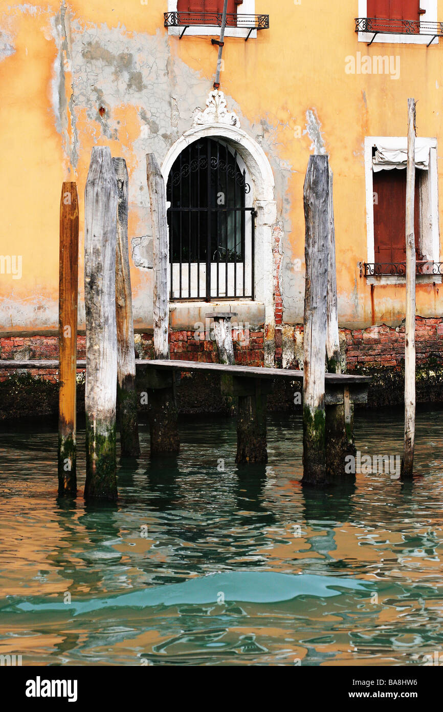 Venetian arched window framed by the wooden posts of a small jetty Venice Italy - Stock Image