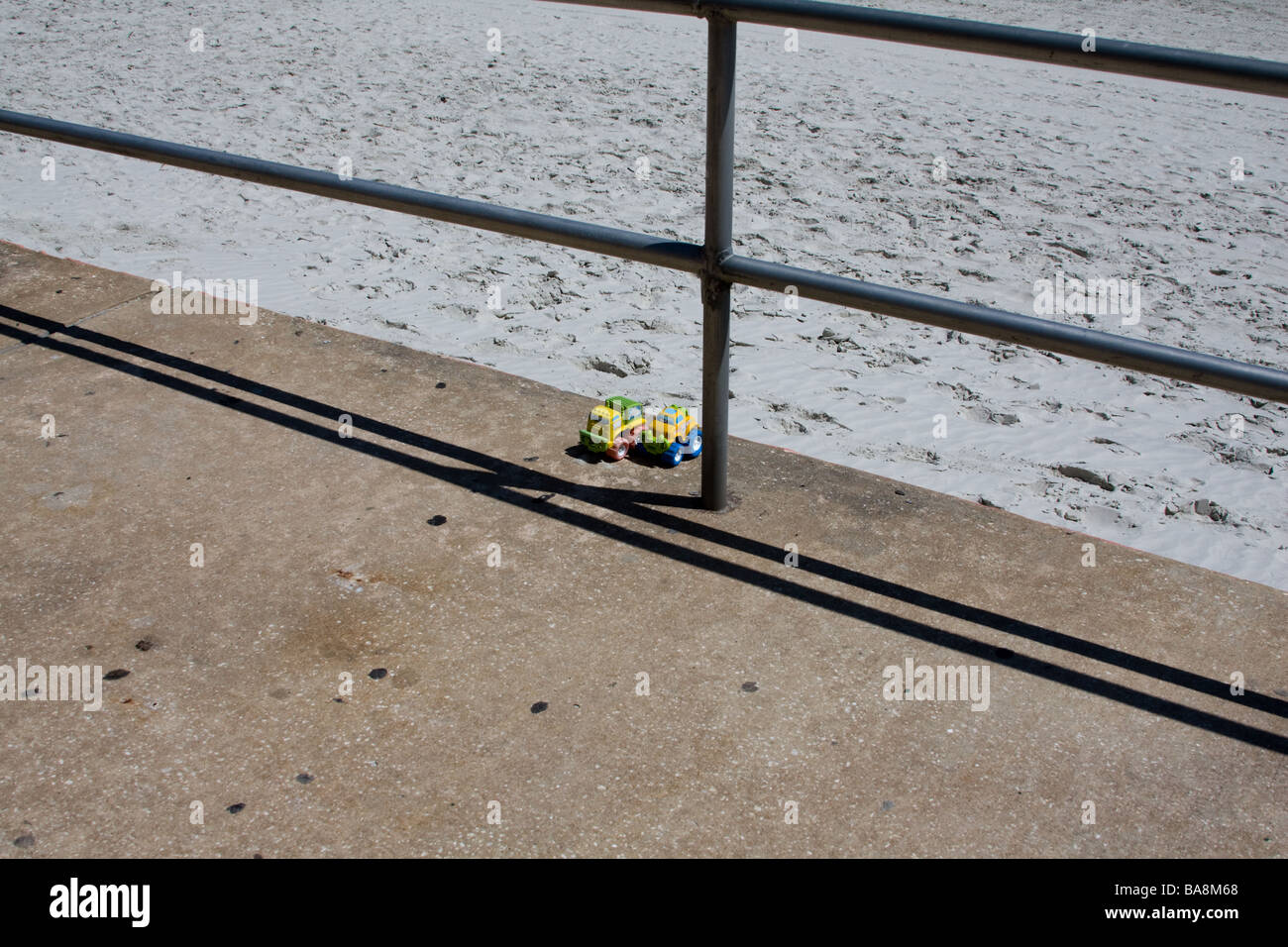 Two forgotten toys left by themselves at the ocean beach waiting for another child to find them and play with them - Stock Image