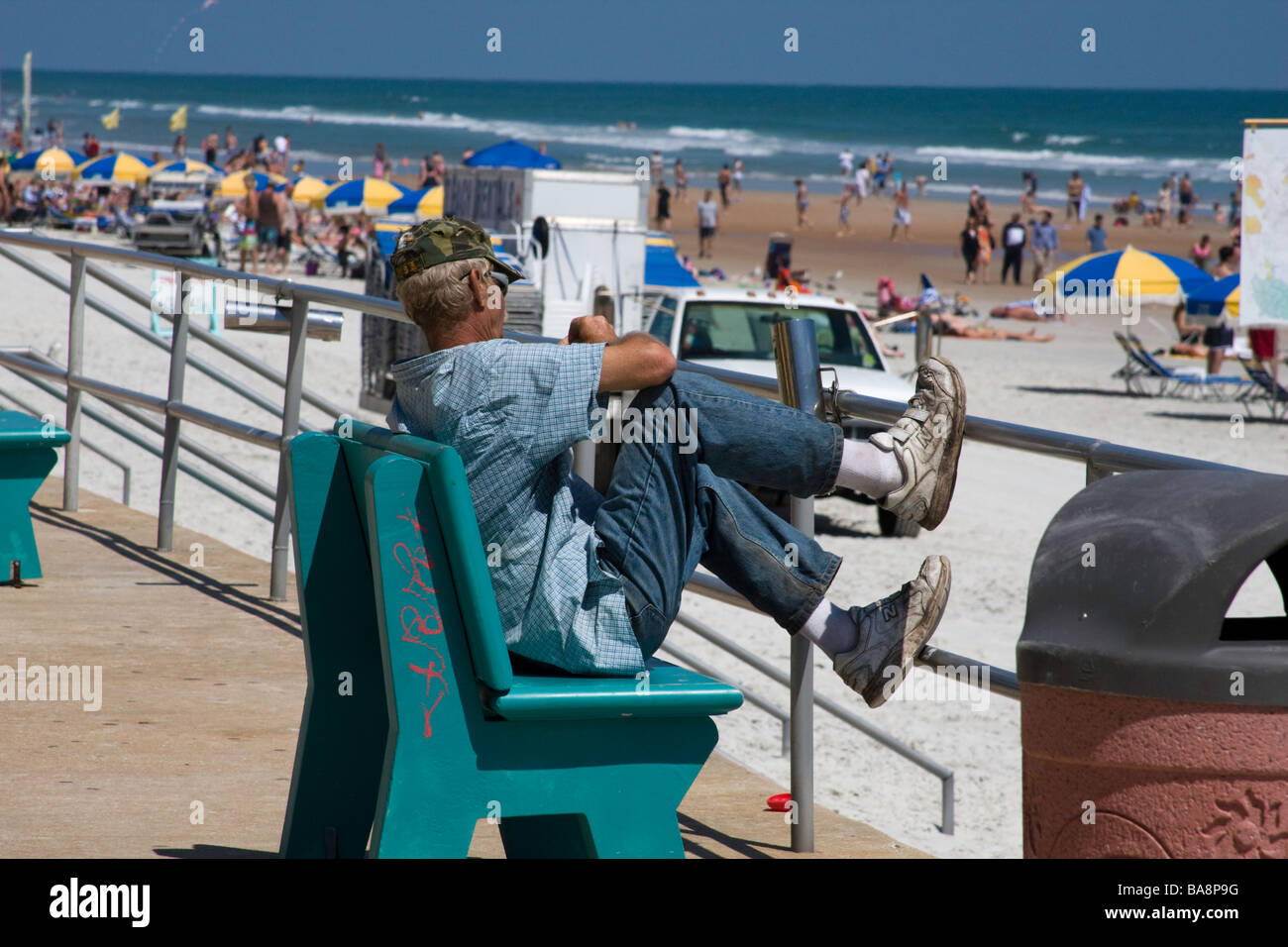Transient homeless person sits on a beach at a tourist location wondering where his next meal will come from - Stock Image