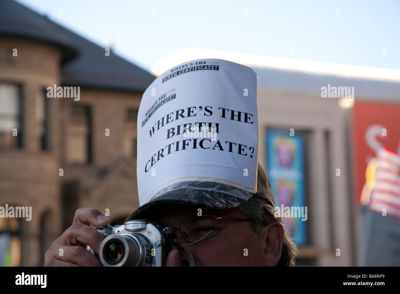 Protester Wearing Wheres The Birth Certificate Sign On His Hat At