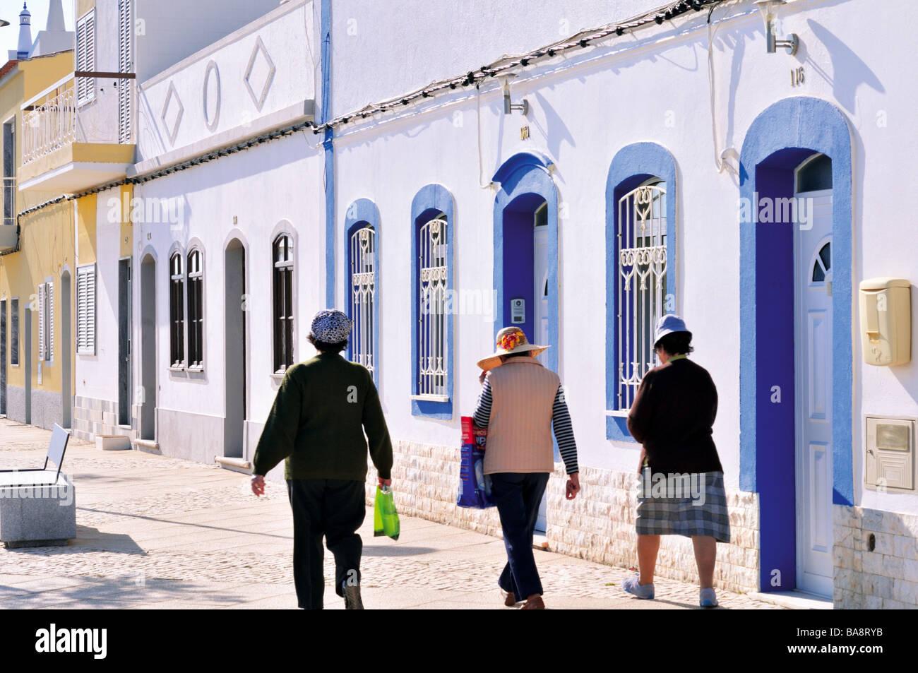 Native women walking in the main street of little fisher village Santa Luzia Stock Photo