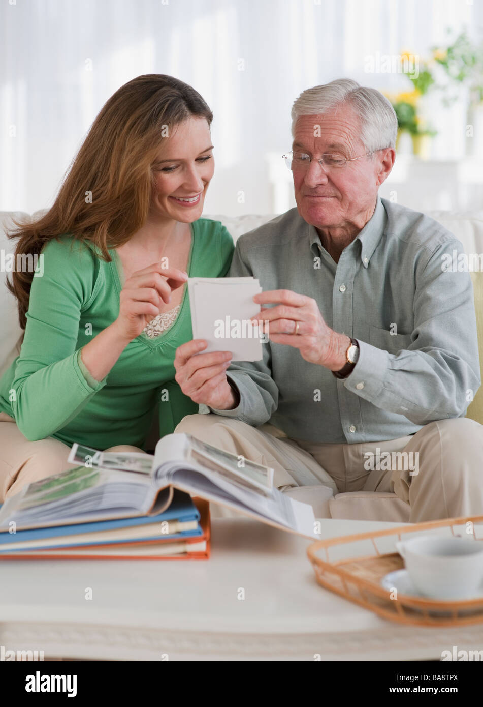 Father and daughter looking at photo albums - Stock Image