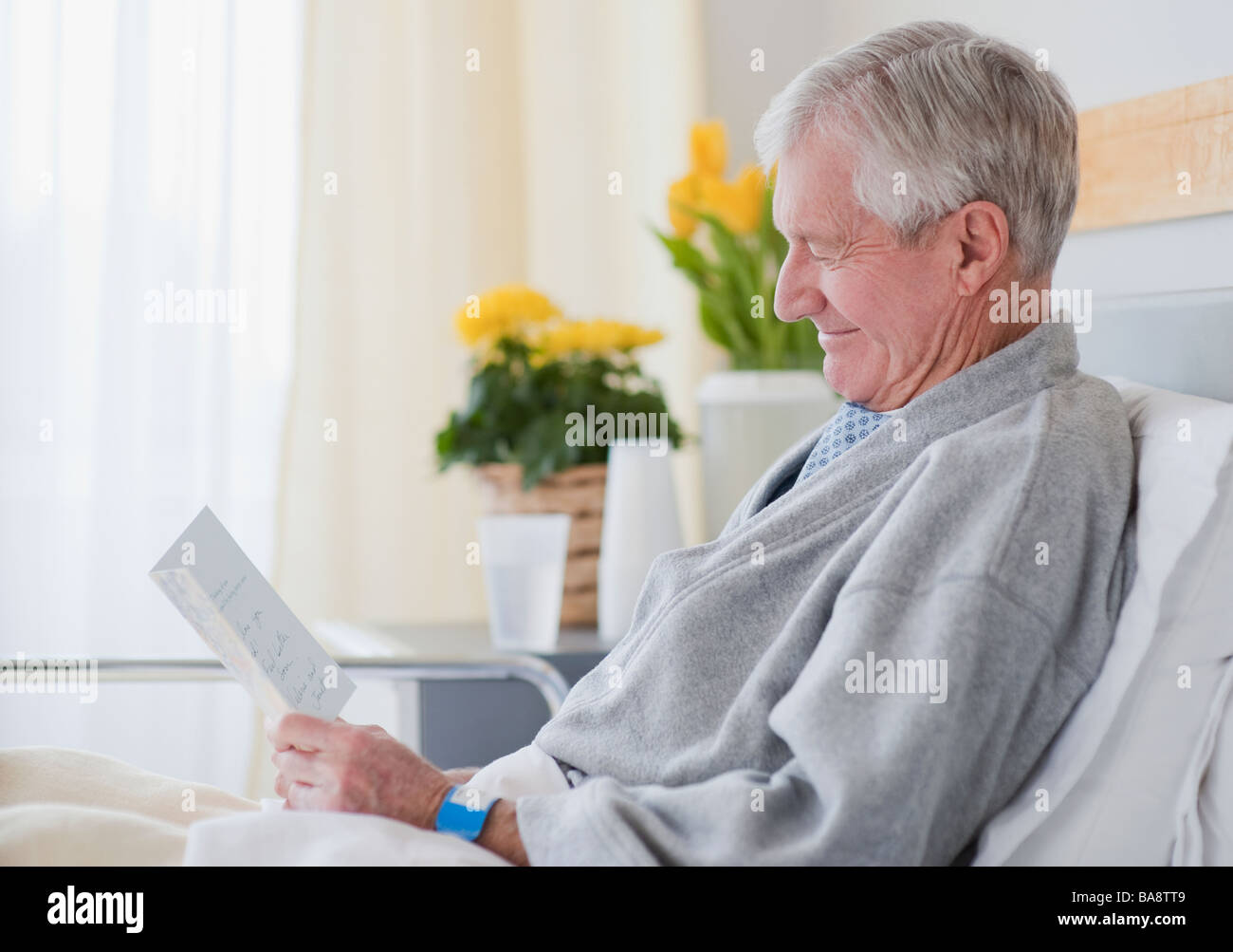 Senior man reading get well card in hospital - Stock Image