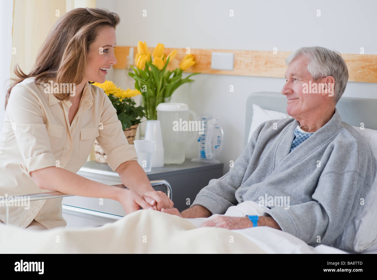 Daughter visiting senior father in hospital - Stock Image