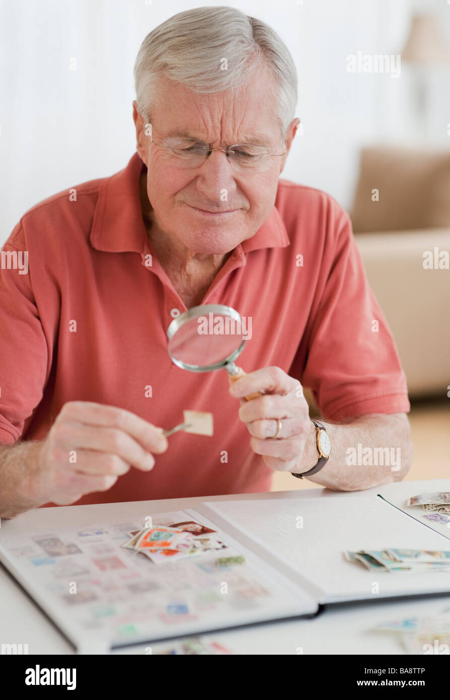 senior-man-looking-at-stamp-collection-B