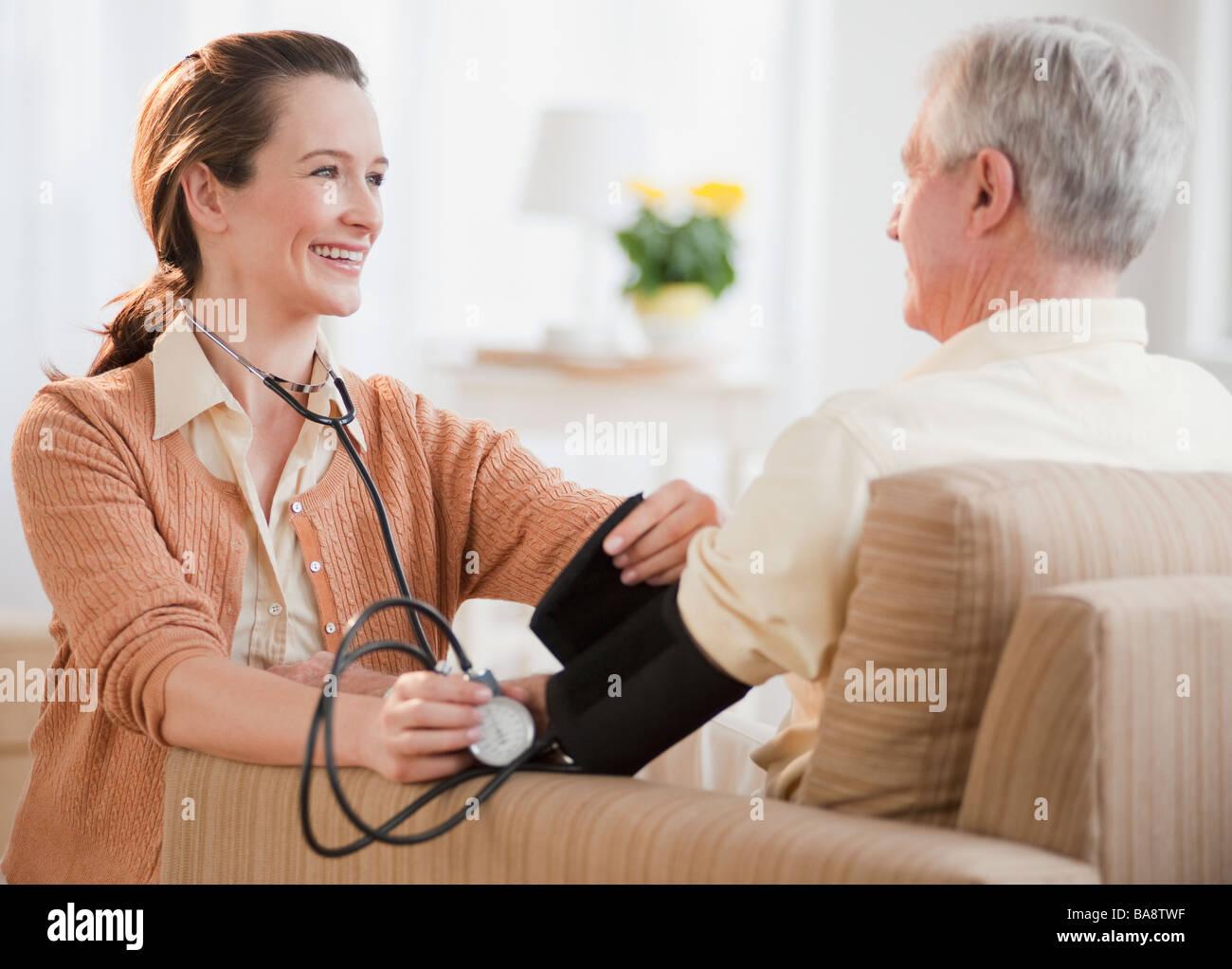 Nurse taking senior man's blood pressure - Stock Image