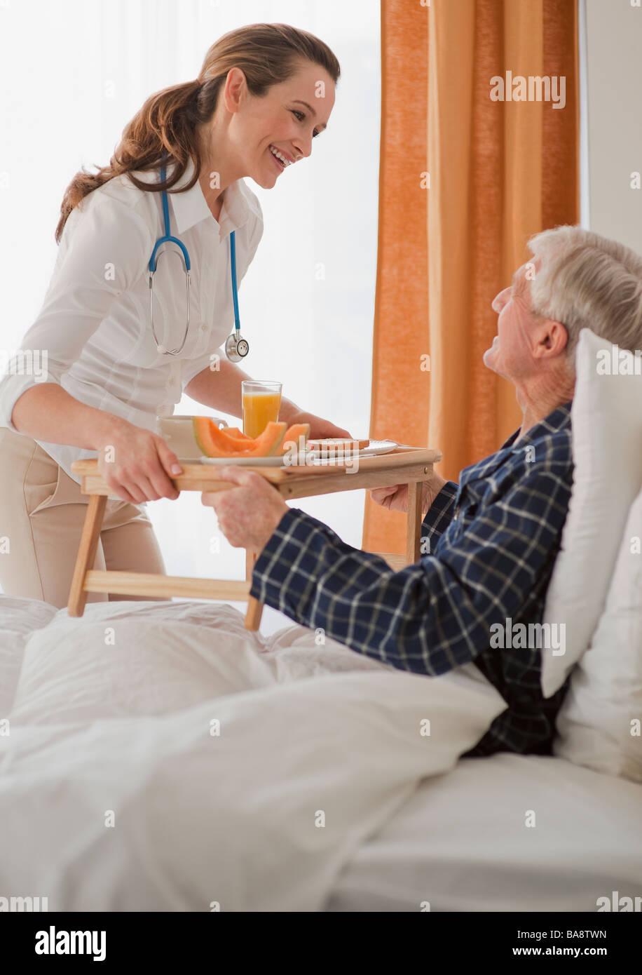 Nurse giving senior man breakfast - Stock Image