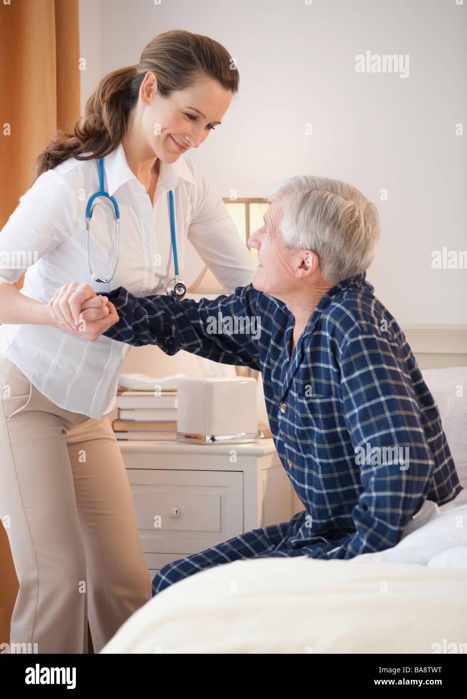 Nurse helping senior man out of man - Stock Image