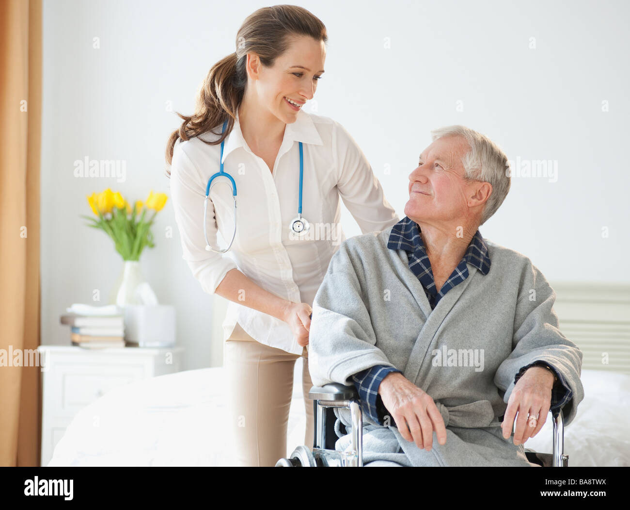 Nurse helping senior man in wheelchair - Stock Image