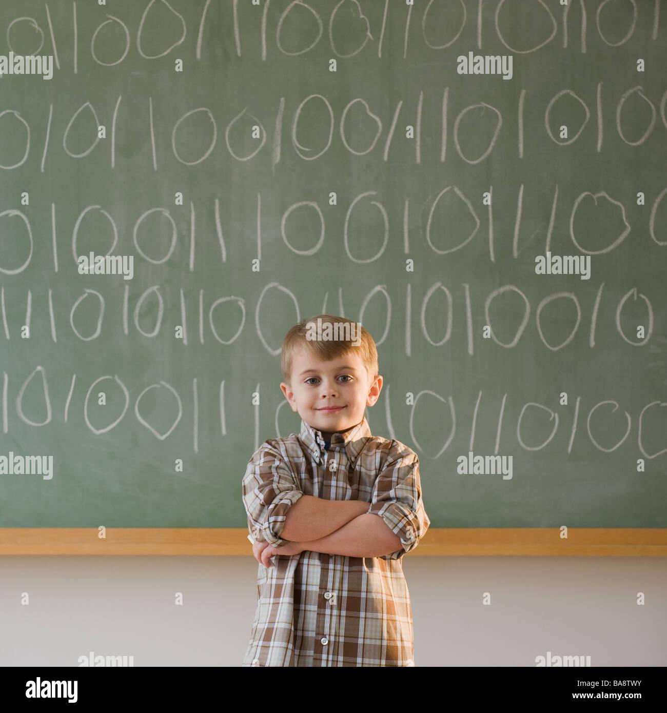 Boy writing binary code on blackboard - Stock Image