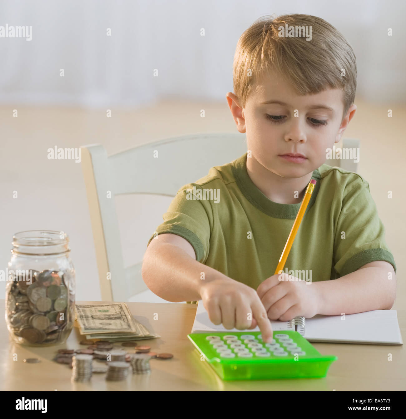 Boy calculating personal finances - Stock Image