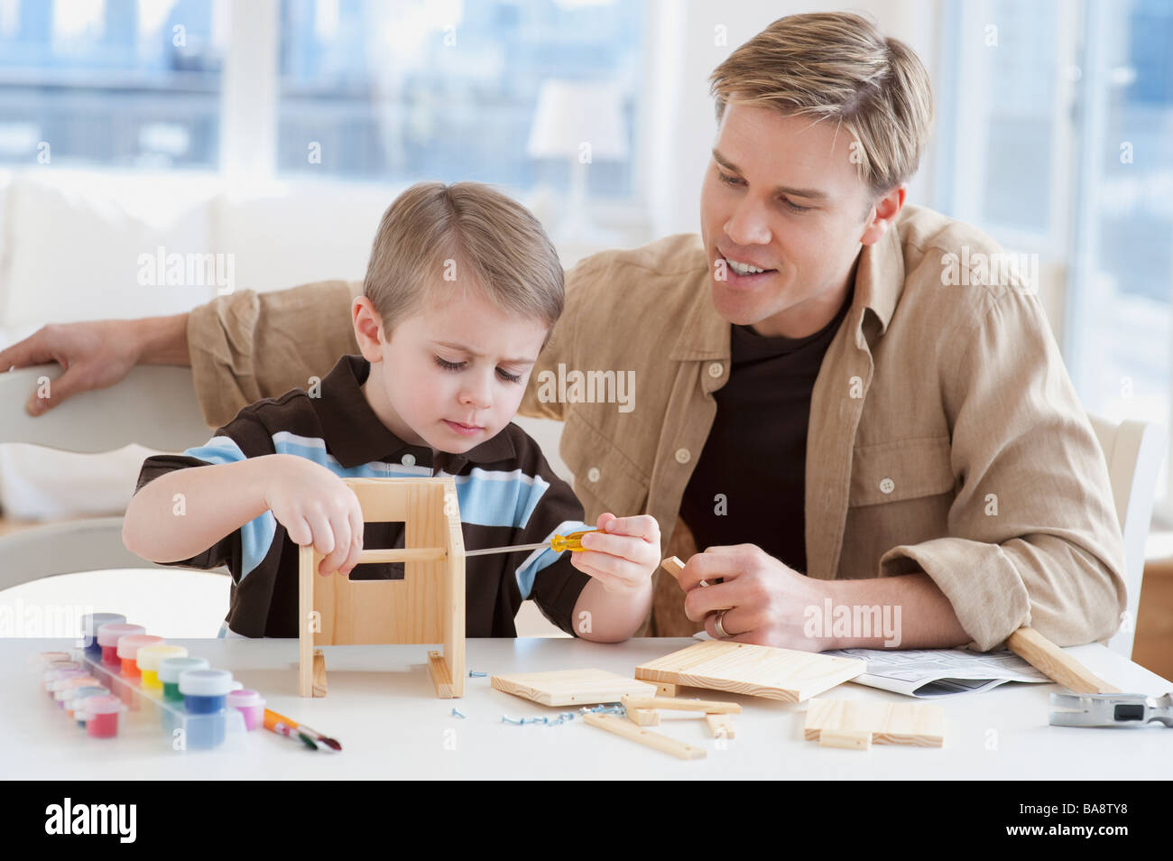 Father and son building wooden model - Stock Image