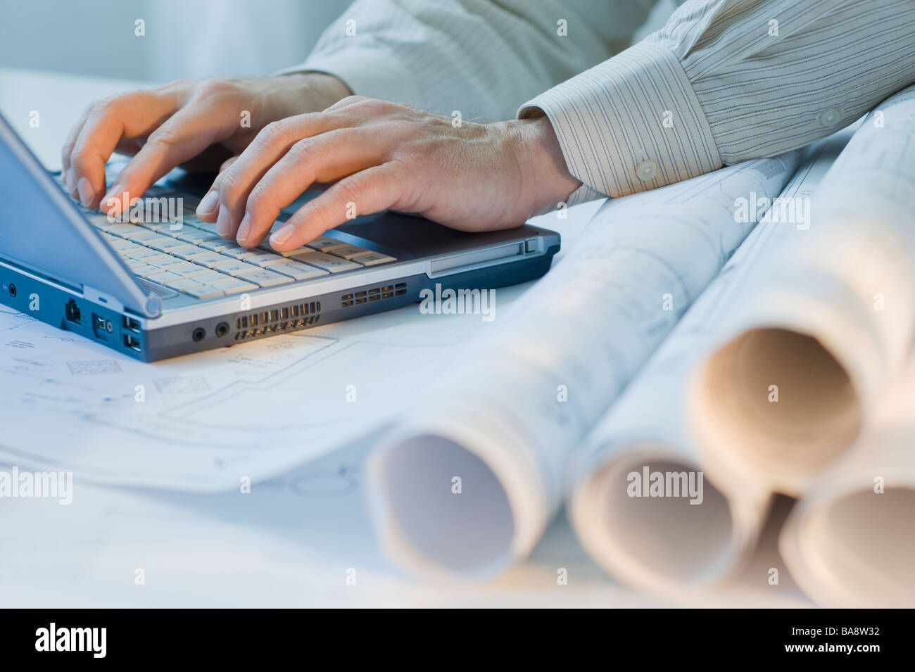 Architect with blueprints and laptop - Stock Image
