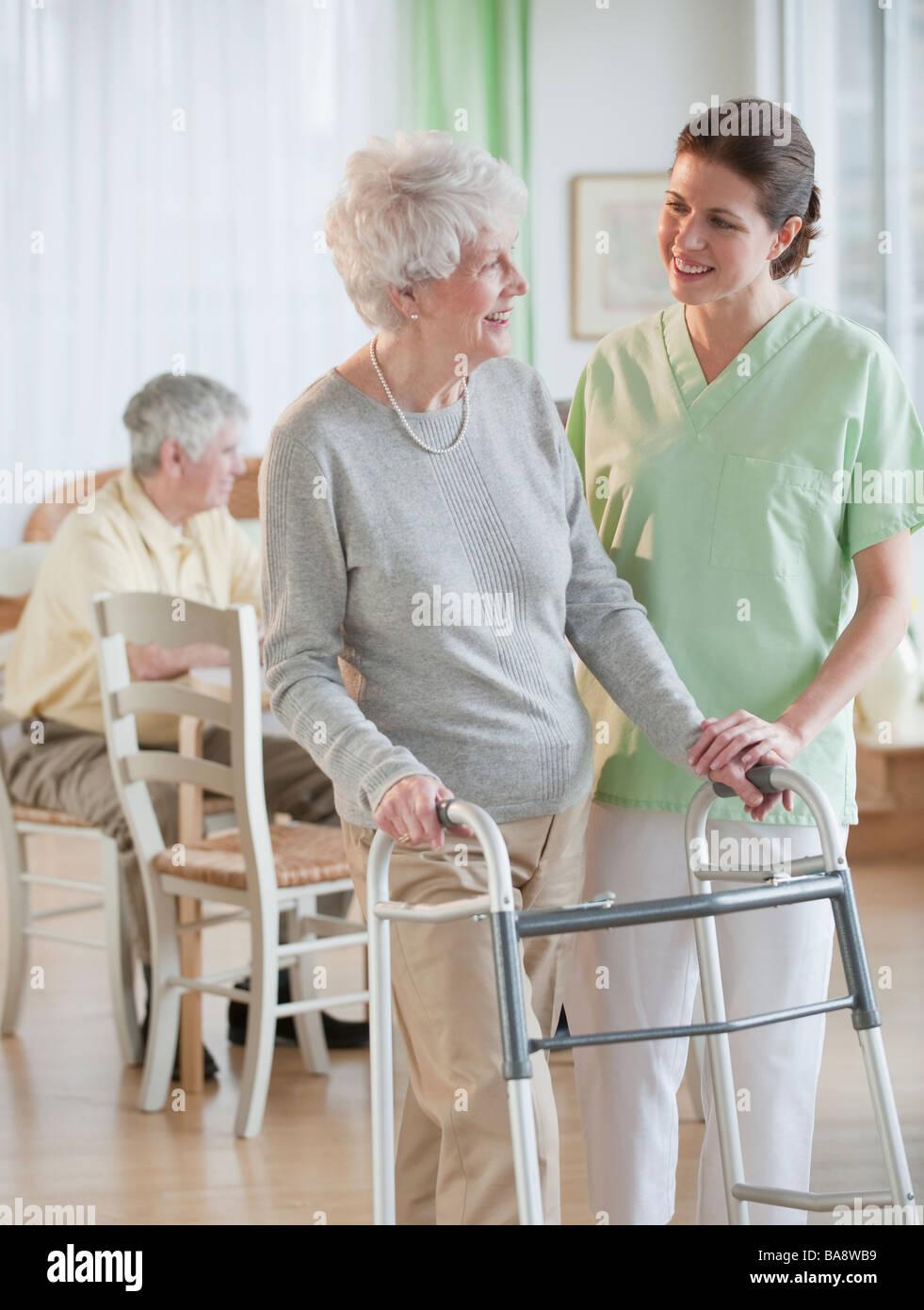Nurse helping senior woman in walker Stock Photo