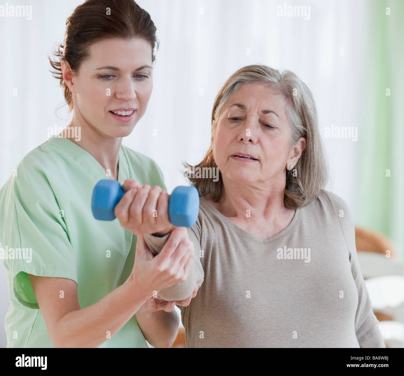 Physical therapist helping senior woman - Stock Image