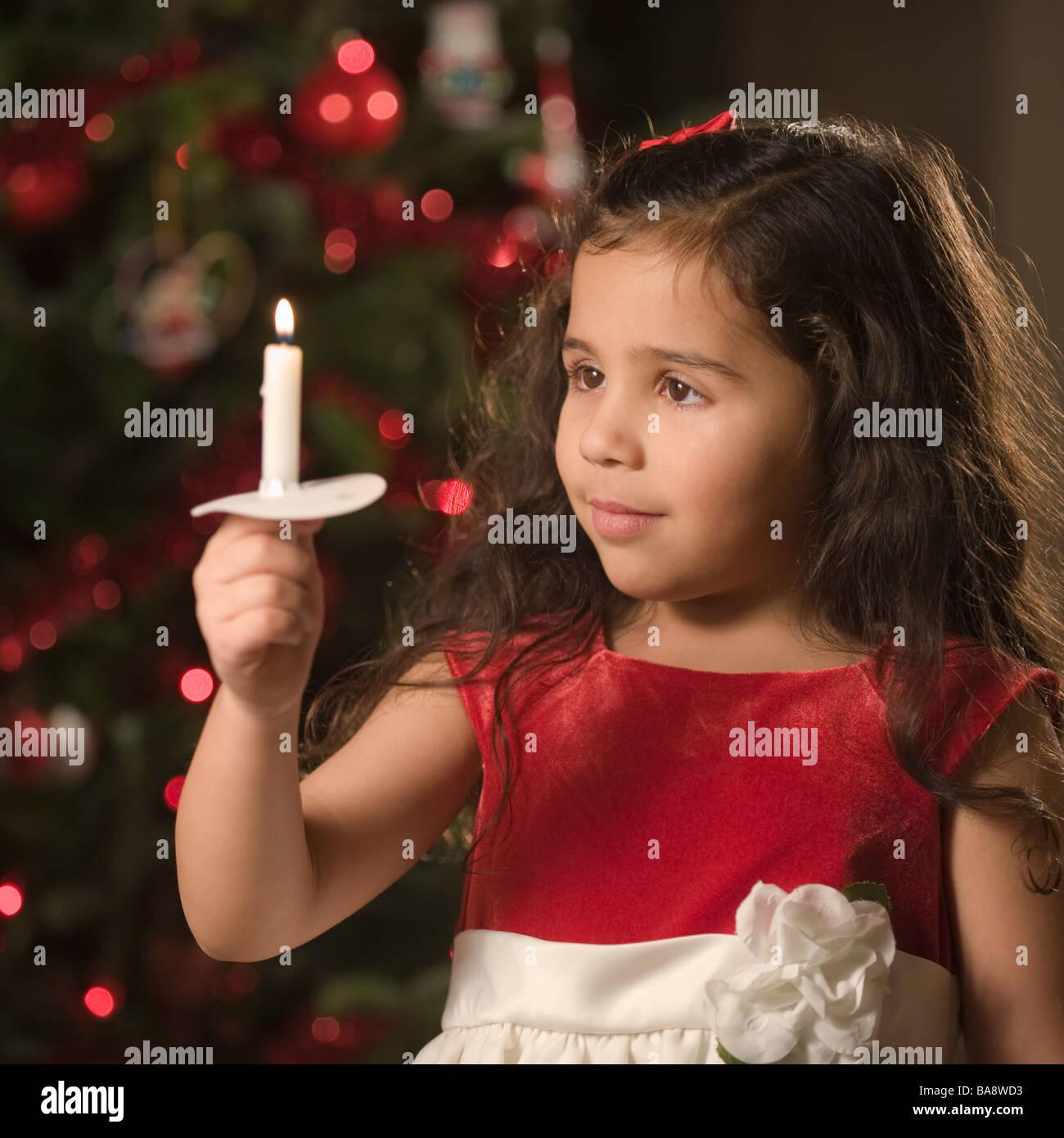 Girl holding Christmas candle - Stock Image